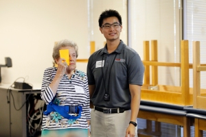 DPT student, Jude Xi, assists a client with a vision test.
